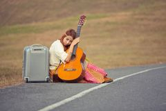 Hippie woman sitting on a countryside road Stock Images