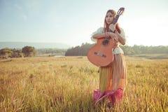 Hippie woman walking in golden field Royalty Free Stock Image