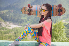 Hippie young and beautiful girl with longboard skateboard at mountain Stock Photos