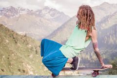 Hippie young and handsome man with longboard skateboard at mountain Stock Image