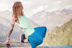 Hippie young and handsome man with longboard skateboard at mountain Royalty Free Stock Photos
