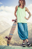 Hippie young and handsome man with longboard skateboard at mountain Stock Photo
