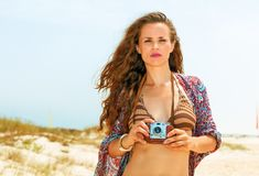 Hippie young woman on seacoast with vintage photo camera Royalty Free Stock Image