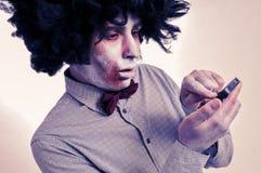 Hippie-Zombie mit einem Afro unter Verwendung eines Smartphone, mit einem Filter E-F Lizenzfreies Stockfoto