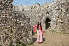 Hippiedame, die an einer Steinwand in einem alten englischen Schloss sich lehnt lizenzfreie stockbilder