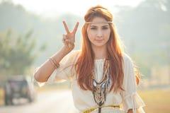 Hippieflicka med fredtecken Royaltyfria Bilder
