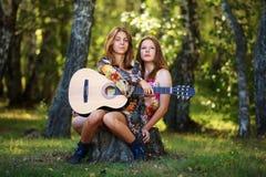 Hippieflickor med gitarren i en skog Royaltyfri Foto