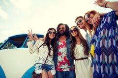 Hippiefreunde über dem Mehrzweckfahrzeugauto, das Friedenszeichen zeigt Stockfoto
