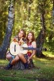 Hippiemädchen mit der Gitarre im Freien Stockbild