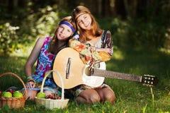 Hippiemädchen mit einer Gitarre im Freien Stockfotos