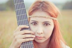 Hippiemeisje met gitaar op gras stock foto's