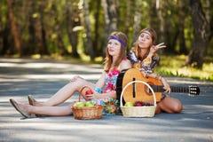 Hippiemeisjes met gitaar in een bos Stock Afbeeldingen