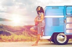Hippiemens het spelen gitaar bij minivan auto op eiland Stock Afbeeldingen