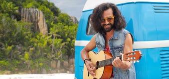 Hippiemens het spelen gitaar bij minivan auto op eiland Royalty-vrije Stock Foto's