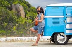 Hippiemens het spelen gitaar bij minivan auto op eiland Royalty-vrije Stock Fotografie