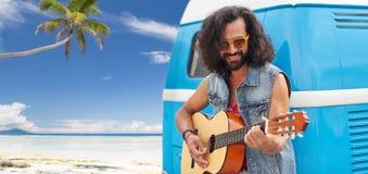 Hippiemens het spelen gitaar bij minivan auto op strand Stock Foto