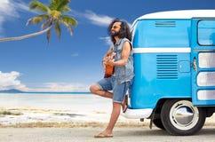 Hippiemens het spelen gitaar bij minivan auto op strand Stock Foto's
