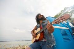 Hippiemens het spelen gitaar bij minivan auto openlucht Royalty-vrije Stock Foto