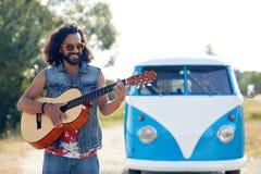 Hippiemens het spelen gitaar over minivan auto openlucht Royalty-vrije Stock Afbeelding