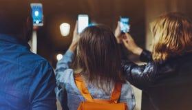 Hippies adultes de groupe employant en plan rapproché de téléphone portable de mains, concept en ligne d'Internet de Wi-Fi dans l image stock