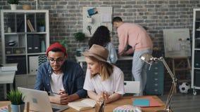 Hippies de fille et de type dans des chapeaux fonctionnant avec l'ordinateur portable parlant dans le bureau moderne banque de vidéos