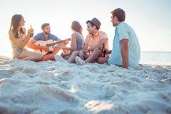 Hippies heureux détendant et jouant la guitare Images stock