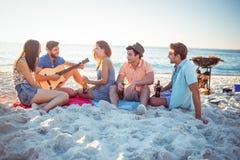 Hippies heureux détendant et jouant la guitare Image libre de droits