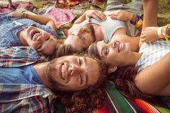 Hippies heureux se trouvant sur l'herbe photo stock