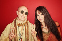 Hippies With Peace Sign. Smiling guru with women gestures peace sign over maroon background stock photos