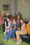 Hippies Sitting on Sofa. Group of four hippies sitting on leather sofa Royalty Free Stock Image