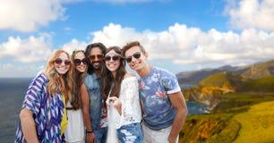 Hippievänner som tar bilden vid selfiepinnen arkivfoton
