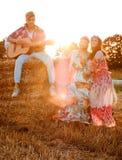 Hippievrienden met gitaar op een tarwegebied stock foto's