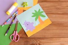 Hippo και φοίνικας εγγράφου applique, χρωματισμένα φύλλα εγγράφου, ψαλίδι, μολύβια, κόλλα, γόμα στο ξύλινο υπόβαθρο με το κενό δι Στοκ Εικόνες