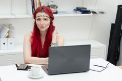 Hippy business model with red hair. Nice young business girl on her work place Royalty Free Stock Photo