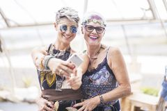 Hippy couple of caucasian beautiful females use a smart phone. Different ages nice attractive people stay together in happy. Leisure activity with friendship royalty free stock image