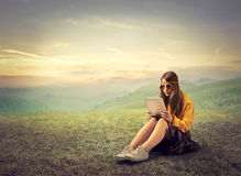 Hippy girl reading with ipad. Hippy teenager with ipad in the countryside Stock Image