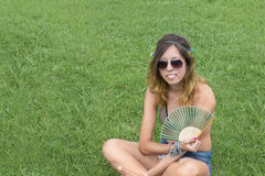 Hippy girl sitting grass holding fan Stock Image