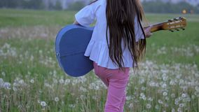 Hippy little girl on sunglasses playing the guitar in outdoor near the city at sunset springtime. emotions and imitate pop artists. Cute hippy little girl on