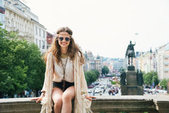Hippy-looking woman sitting on parapet on Wenceslas Square Royalty Free Stock Images