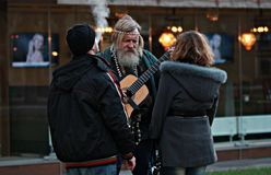 Hippy Man Plays Guitar in Odessa, Ukraine. A hippy in Odessa, Ukraine plays guitar as a couple looks on. The man is smoking and the woman is listening. The Stock Photography