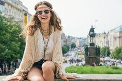 Hippy-olhando o turista da mulher que senta-se no parapeito de pedra em Praga Imagens de Stock