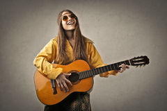 Hippy playing the guitar. Smilinghippy teenager playing the guitar Royalty Free Stock Photography