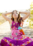 Hippy purple dress teen girl relaxed outdoors. Sitting over the park wood Royalty Free Stock Photos
