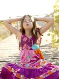 Hippy purple dress teen girl relaxed outdoors. Sitting over the park wood Royalty Free Stock Photo