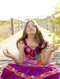 Hippy purple dress teen girl relaxed outdoors. Sitting over the park wood Royalty Free Stock Images