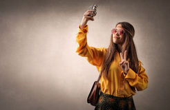Hippy teenager making a selfie. Young hippy girl posing for a picture with her smartphone Stock Photos