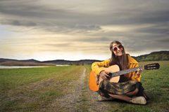 Hippy teenager playing the guitar. Young hippy girl having fun while playing the guitar Royalty Free Stock Images