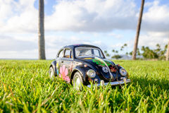 Hippy tinplate car on vacation at sunset. Tin model car on fresh lawn with sun star reflections Royalty Free Stock Photo