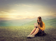 Hippy using a tablet. Hippy teenager using a tablet in the countryside Stock Photos
