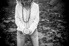 Hippy woman taking a shell on her hands, black and white. Black and white image of a woman taking a shell on her hands. Hippy style and clothes with long Stock Photos